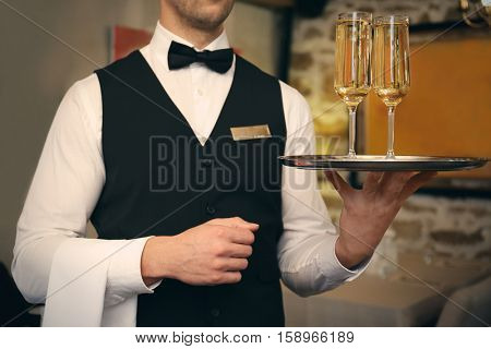 Waiter serving champagne at restaurant, close up view