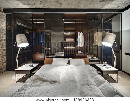 Loft style interior with brick wall and concrete ceiling. There is a bed with white pillows and blankets, glowing lamps, wardrobe with glass sliding doors, tables, parquet and a carpet on the floor.