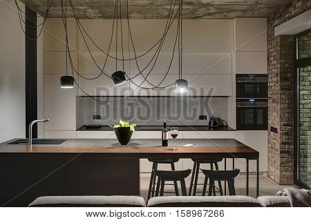 Kitchen in a loft style with concrete and brick walls. There is a kitchen island with a sink, plant and black chairs, light lockers with built-in oven and fridge, dark tabletop with stove and teapot. poster