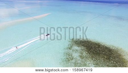 Maldives island Indian Ocean jet ski wakeboarding aerial top view.