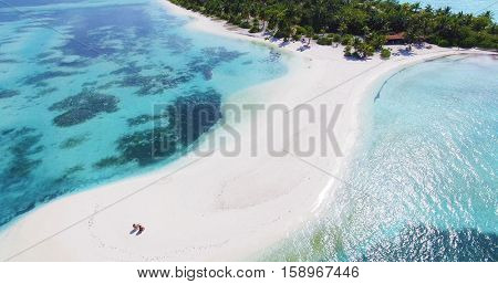 Couple on an empty beach. Panoramic landscape seascape aerial view over a Maldives Male Atoll island. White sandy beach seen from above.