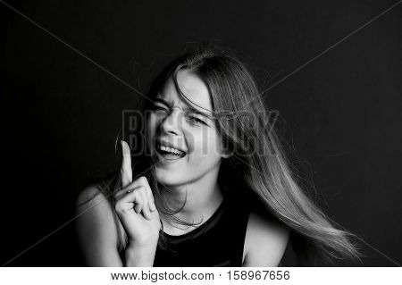 Young beautiful girl with long hair in Studio. Faces finger with humor . BW
