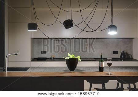 Loft style kitchen with a concrete wall. There is a kitchen island with a sink, plant, bottle and glass, black chairs, light lockers, dark tabletop with stove and teapot, hanging black glowing lamps. poster