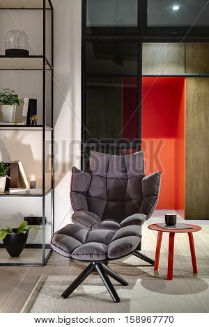 Design soft armchair on the background of glass partitions and the red entrance door. Next to it there is a small red table with notebook and cup, shelves with books, plants, decorations, candle.