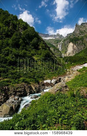 Nature view, cool mountain river stream flowing from under the glacier on background of mountain sierra