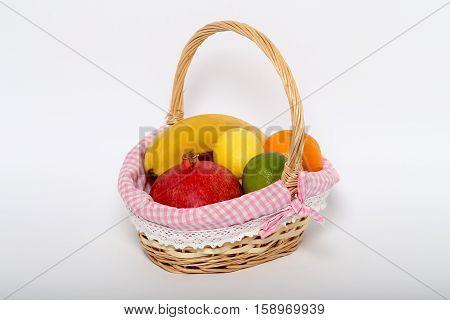 Яркие свежие цитрусовые фрукты в корзине с ручкой