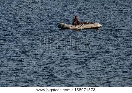 Man, and a Dingy is a photograph about a lone seafarer in his rubber raft in the ocean where he depends completely on his own abilities to survive.