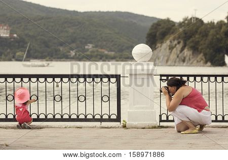 Woman makes photo of a daughter outdoors in sommer near nice lake and mountains.