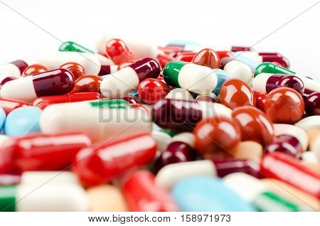 Medical theme. Multicolored Pills and Capsules on the White Surface. Closeup