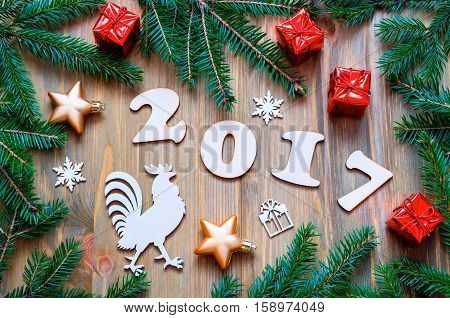 Happy New Year 2017 background with 2017 figures,Christmas toys, fir tree branches and rooster- New Year 2017 symbol.Concept of Happy New Year 2017 holiday- New year of red rooster. Flat lay, top view