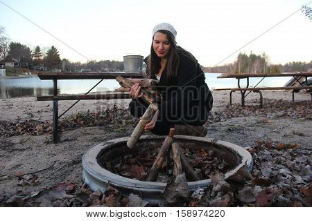 A woman places wood in a firepit