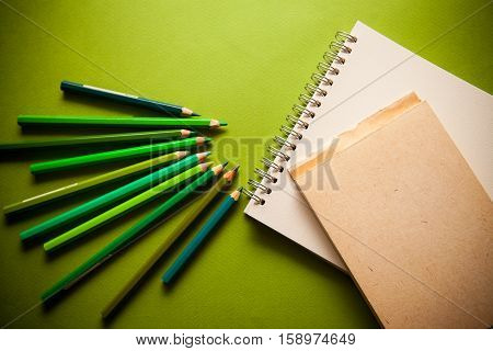green shades pensils and notebook on green paper