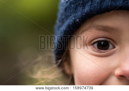 Young girl in warm blue wool hat. Half face of child in woolly winter hat smiling with only eye fully in frame