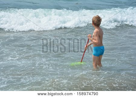 Small blond boy with blue swimming trunks stands with a fishing-net in the water and waits for the sea - wave