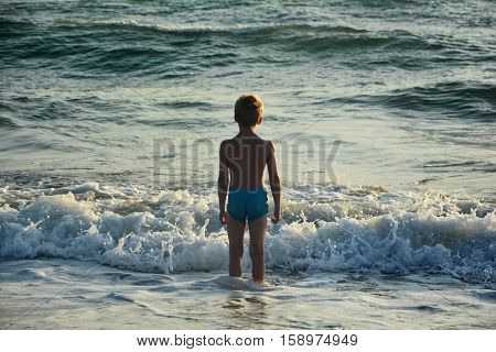 Small blond boy with blue swimming trunks stands in the water before a wave and looks to the sea