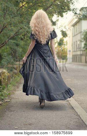 Beautiful elegant blonde woman in black maxi long dress, going away, outside