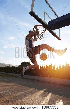 Young Man Jumping And Making A Fantastic Slam Dunk Playing Stree
