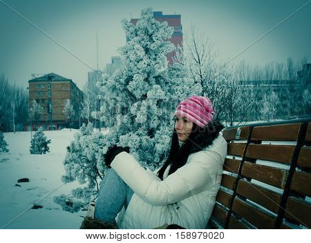 Girl Thoughtfully Looking Into The Distance, Sitting On A Bench In The Winter.