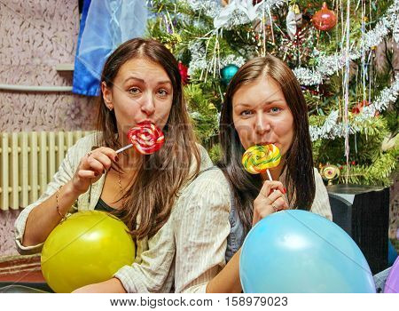 Two young girls sucking candy in his mouth sitting under the tree