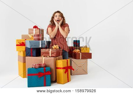 Young surprised beautiful curly girl among gift boxes Isolated Copy space