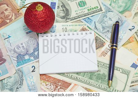 Blank notebook page with Christmas decoration and pen on background from world currencies