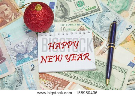 Notebook page with text HAPPY NEW YEAR background from different world Currencies