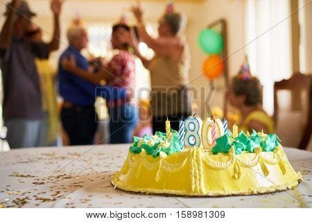 Group of old friends and family celebrating senior man 80 birthday party in retirement home. Happy patients dancing in hospice. Focus on cake