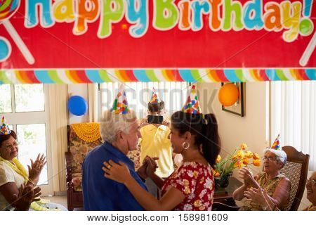 Family celebrating senior man birthday in hospice. Patient dancing with daughter in hospital and child taking photo.