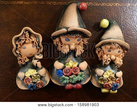 New year and Christmas. Festive gnomes. Three gnomes with flowers - two boys and the girl. Clay. Interior. Decor.