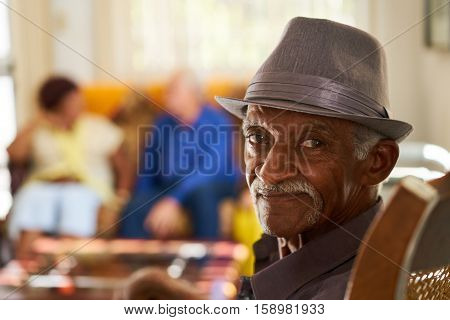 Portrait of elderly black man looking at camera in retirement home with group of friends in background. Patients relaxing in hospice for seniors.
