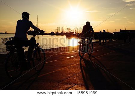 Beautiful quay near the sea on sunset. Silhouettes of people riding bicycles near the water. Ships yachts and catters moored to the pier.