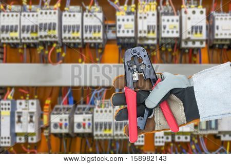 Hand In Glove Holding  Wire Stripper With Control Panel Cabinet