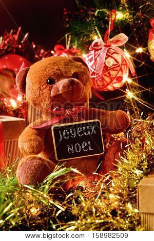 closeup of a teddy bear with a chalkboard with the text joyeux noel, merry christmas written in french, and some gifts under a christmas tree ornamented with lights, balls and tinsel