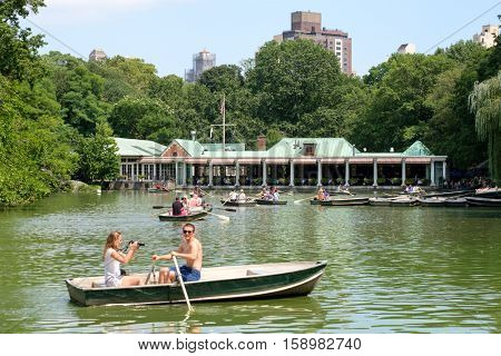 NEW YORK,USA - AUGUST 19,2016 : Rowboats at The Lake with a restaurant on the background at Central Park in New York City