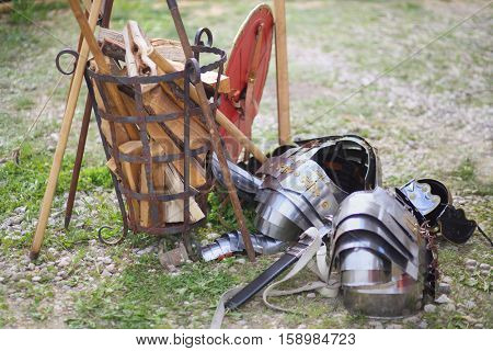 MOSCOW - JUN 06, 2015: Carapace, sword and shield Roman soldier on the grass near the forged baskets of firewood at the festival Times and epoch: Ancient Rome in Kolomenskoye
