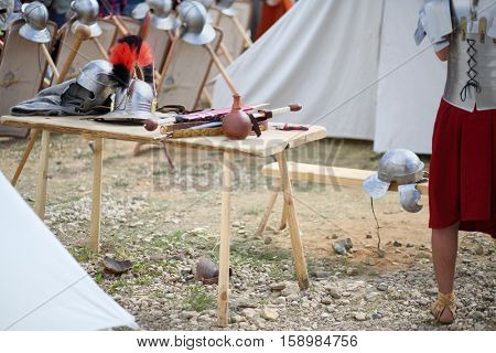 MOSCOW - JUN 06, 2015: Helmet and swords of Roman soldiers on a wooden table in the camp at the festival Times and epoch: Ancient Rome in Kolomenskoye