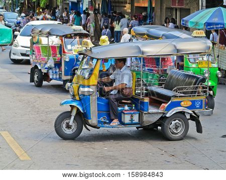 BANGKOK, THAILAND - OCTOBER 2, 2016:A three wheeled tuk tuk taxi on a street in the Thai capital on October 2, 2016 in Bangkok, Thailand. Tuk tuks are commonly used in transporting people.