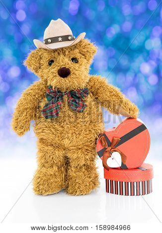 Teddy bear with Red heart shaped gift box on blue bokeh background