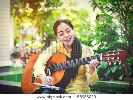 Pretty songwriter tooth smiling and having fun enjoy hobby concept. Asian woman writing on note paper with acoustic guitar near by outdoor at daytime with bright sunlight. Vintage effect tone.