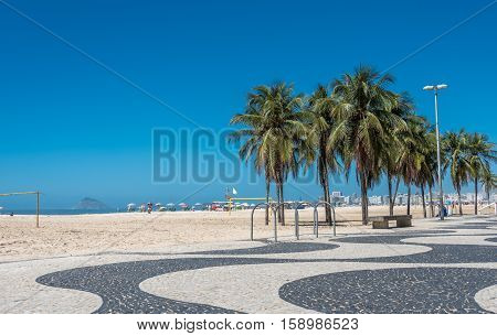 Copacabana beach with white sand, blue sky, green palms and mosaic floor, black and white Portuguese pavement in Rio de Janeiro, Brazil