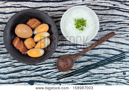 Rice gruel and stewed boiled egg with tofu and streaky pork served .