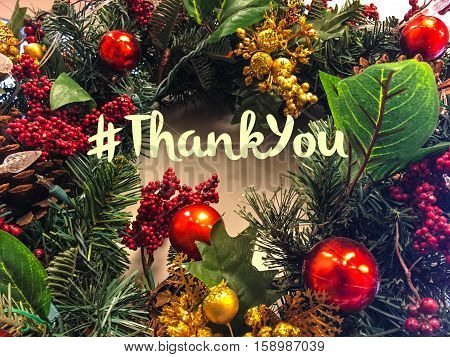 Christmas or seasons greetings thank you card with hashtag to send seasons greetings to social network friends, followers, community or clients at the end of the year thank you and seasons greetings on Christmas wreath with room for copy space
