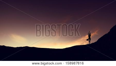 Silhouette mountain edge young woman practicing yoga on mountain in sunrise