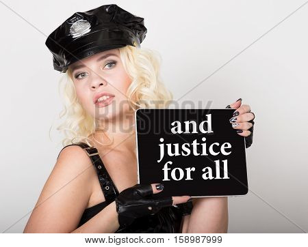 and justice for all written on screen. technology, internet and networking concept. beautiful female police officer holding pc tablet.