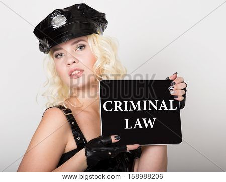 criminal law written on screen. technology, internet and networking concept. beautiful female police officer holding pc tablet.