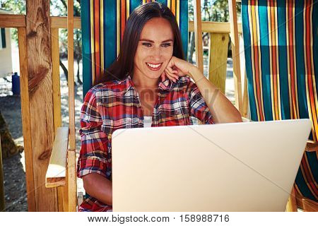 Mid shot of tanned smiling woman in casual outfit looking at the screen of laptop while sitting on a chair. Caucasian woman sitting on a summer beach chair.