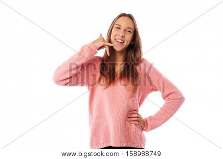 Mid shot of enthusiastic teenager imitating a phone call with his hand while posing at the camera. Beautiful model posing in studio over white background