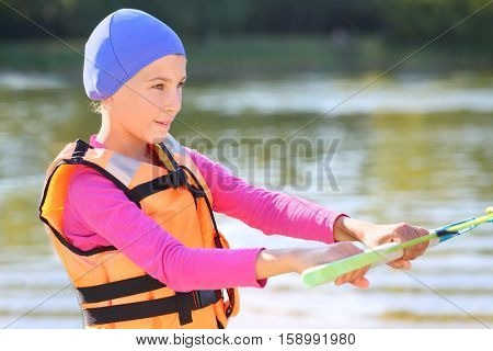 Portrait of girl in life jacket holding a foul in front of water