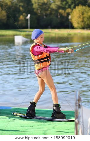 Girl in life jacket standing on the board and hold for a foul near pond