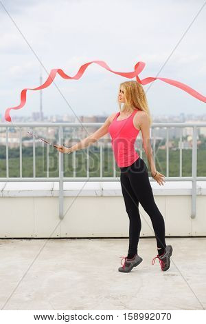 Beautiful blonde with red curly ribbon standing on tiptoe on the roof of a multistory building